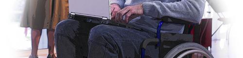 Photo partielle d'une personne en fauteuil roulant utilisant un ordinateur portable